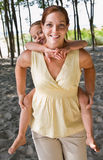 Mother giving daughter piggy back ride Stock Image