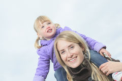 Mother giving daughter piggyback ride in autumn Stock Photography