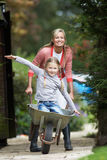 Mother Giving Daughter Ride In Wheelbarrow Stock Photos
