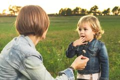 Mother giving a flower to her little daughter in the field stock photography
