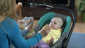Mother giving food to her adorable child at home. 4K stock footage
