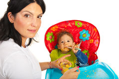 Mother giving food to messy baby Royalty Free Stock Photos