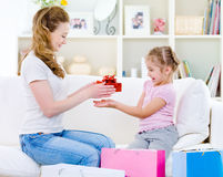 Mother giving a gift for her daughter Royalty Free Stock Photos