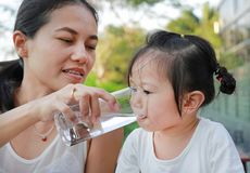 Mother giving glass of water to her child. stock image