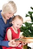 Mother is giving a gold gift to little baby Stock Image