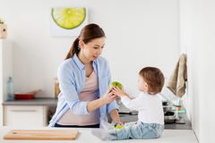 Mother giving green apple to baby at home kitchen. Family, food, healthy eating, people and motherhood concept - happy young mother giving green apple to baby at Stock Images