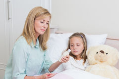 Mother giving her daughter cough medicine Stock Photography