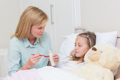 Mother giving her daughter cough medicine Stock Images