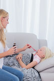 Mother giving her daughter cough medicine Stock Image