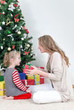 Mother giving her daughter gift. Stock Images