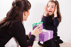 Mother giving her daughter a gift Stock Image