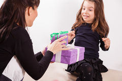 Mother giving her daughter a gift Royalty Free Stock Photos