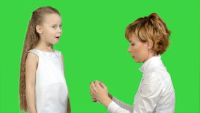 Mother giving her daughter medicine on a green screen, chroma key stock video footage