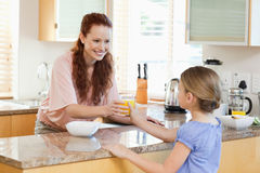 Mother giving her daughter orange juice Royalty Free Stock Photos