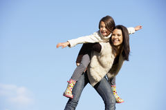 Mother Giving Her Daughter A Piggy Back Ride Stock Photos
