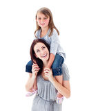 Mother giving her daughter piggyback ride Stock Images