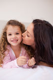 Mother giving her little daughter a kiss Stock Photo