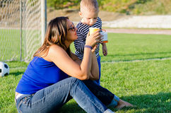 Mother giving her small son a drink Royalty Free Stock Photos