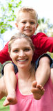 Mother giving her son a piggyback ride Royalty Free Stock Image
