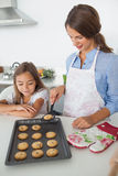 Mother giving a homemade cookie to her daughter Royalty Free Stock Images
