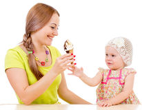 Mother giving ice cream to little girl sitting at table Stock Photography