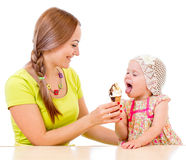 Mother giving ice cream to little girl sitting at table Royalty Free Stock Photo