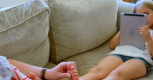 Mother giving a leg massage to her daughter in living room 4k