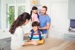 Mother giving lunch box to son with father carrying daughte Stock Photo