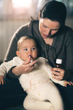 Mother giving medicine to baby Stock Images