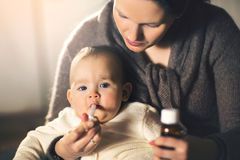 Mother giving medicine to baby stock photos