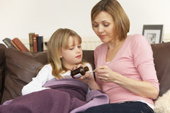 Mother Giving Medicine To Sick Daughter Stock Photography
