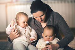 Mother giving medicine to twins babies royalty free stock photo