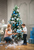 Mother giving a present to the oldest son, baby boy touching bauble on Christmas tree. Young mother giving a present to the oldest son, baby boy touching bauble Stock Images