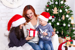 Mother giving presents to her kids in front of Christmas tree Royalty Free Stock Photography