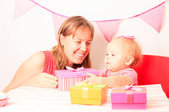 Mother giving presents to little daughter on Royalty Free Stock Image