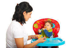 Mother giving puree to her baby. Boy and having conversation against white background Stock Photography