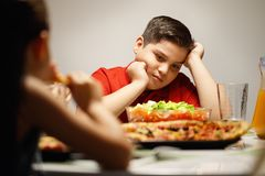 Mother Giving Salad Instead Of Pizza To Overweight Son. Hispanic family with mom, fat son and daughter having dinner at home, eating salad and pizza. Latino Stock Photography