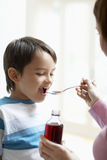 Mother Giving Son Cough Syrup Royalty Free Stock Photos