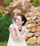 Mother giving son piggyback Stock Photo