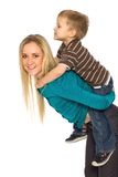 Mother Giving Son Piggyback Ride Stock Images