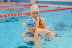 Mother giving son a swimming lesson in pool indoors.  Stock Images
