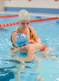 Mother giving son a swimming lesson in pool indoors.  Stock Photo