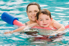 Mother giving son a swimming lesson in pool. During summer Stock Photo