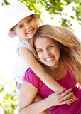 Mother giving to her daughter in the park. Young mother giving her daughter piggyback ride in the park Royalty Free Stock Photography