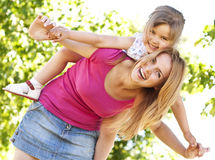 Mother giving to her daughter in the park. Young mother giving her daughter piggyback ride in the park Stock Images