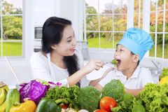Mother giving vegetables on her son Stock Photography