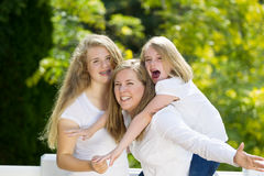 Mother giving younger daughter piggy back ride Stock Photos