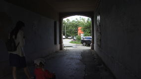 Mother goes through the arch with her daughter on a tricycle, slow motion. stock video