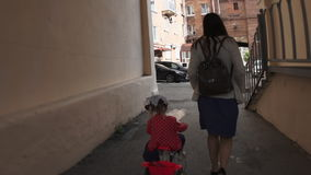 Mother goes through the arch with her daughter on a tricycle, slow motion. stock video footage