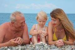 Mother and grandfather with child lie on sea coast Royalty Free Stock Image